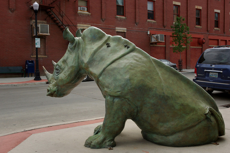 """Bronze statue of a rhinoceros by Dollores Shelledy. Sadly, someone has broken off the """"tickpicker"""" birds which were once on this side - only their feet remain on the rhino's back.<br /> Sheridan, Wyoming."""