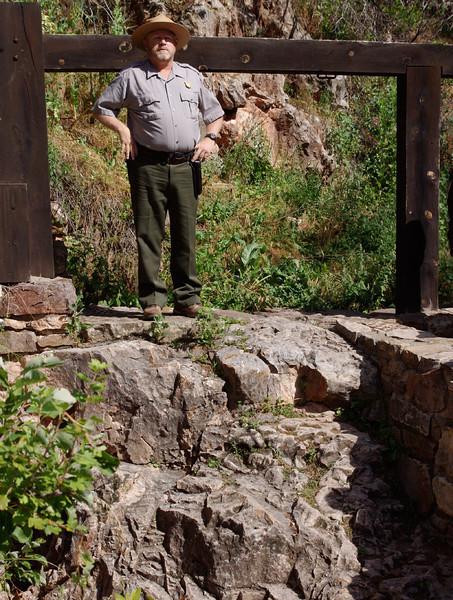 Park ranger at the natural entrance to Wind Cave; Wind Cave National Park, South Dakota.