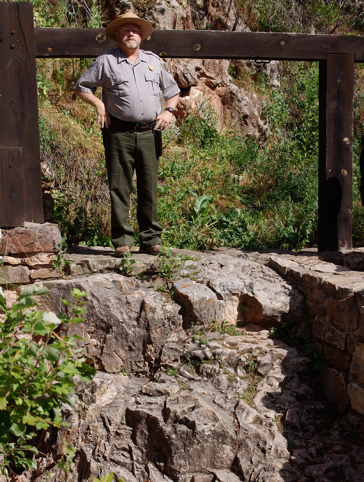 Park ranger at the natural entrance to Wind Cave; Wind Cave National Park, South Dakota.