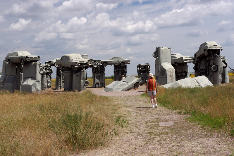 "Rita confronts Carhenge - a roadside attraction near Alliance, Nebraska featuring: ""Thirty-eight automobiles placed to assume the same proportions as Stonehenge"""