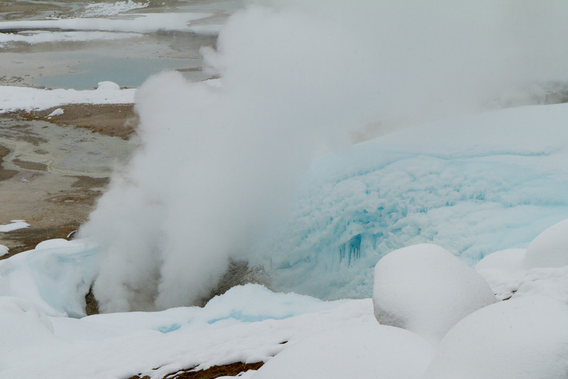 Geyser near the museum of Porcelain Basin vents large amounts of steam continuously. The blue color of the snow is from dense compaction