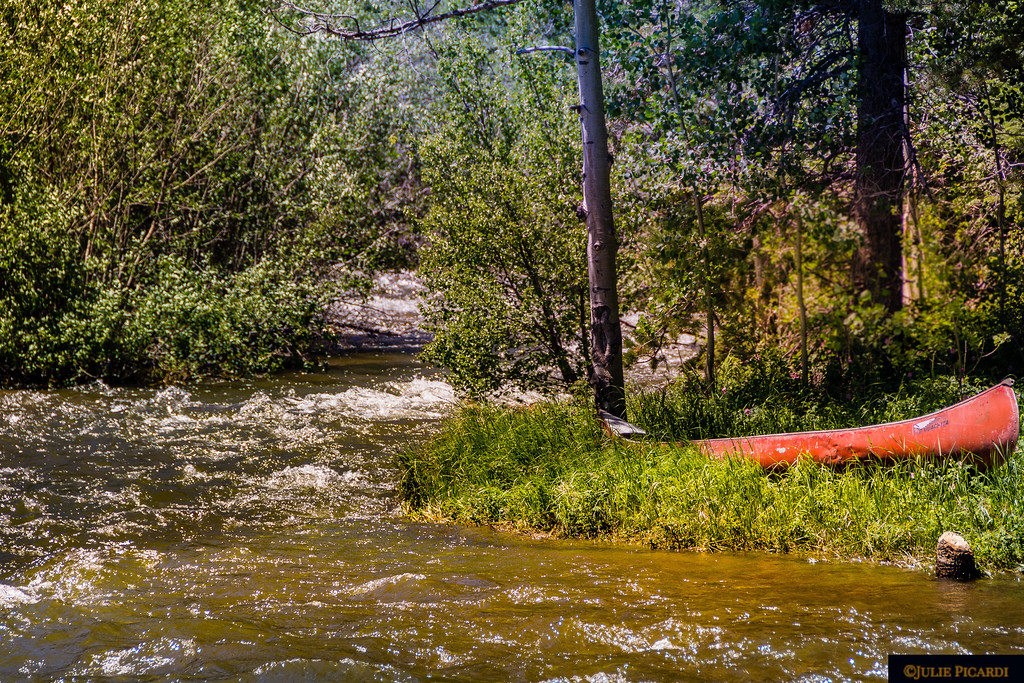 A forgotten canoe waits by the fast running creek.