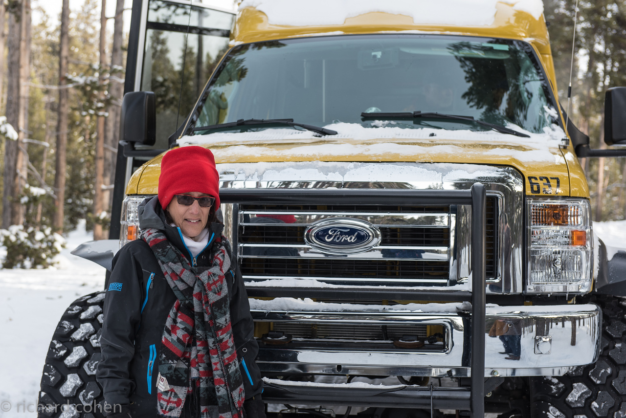 Lisa next to our snow coach. They use Ford F350 trucks with giant snow tires at very low inflation to get around on the snow packed (they don't plow) roads.