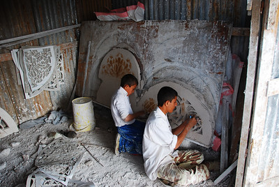 """Inside a tiny factory where the window tracery (""""takhrim"""") for stained glass windows is made.  Template patterns are copied onto slabs of wet gypsum plaster then the inner pieces are cut out, leaving spaces for the coloured glass to be inserted later."""
