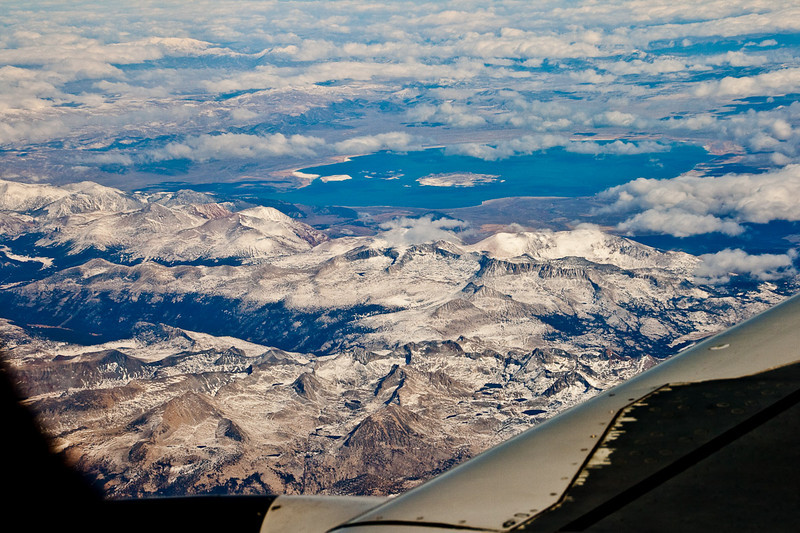 Flying over the snowy Sierra Nevada range in California. You can see Mono Lake just above center of the photo.