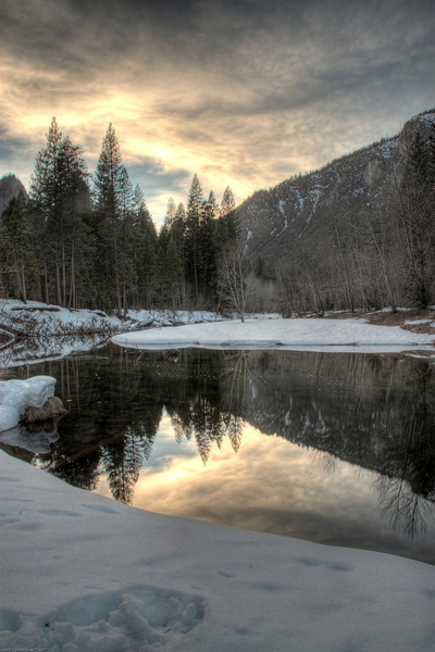 <h3>Reflection in The Merced River</h3>The sun is setting over the Yosemite Valley.  The Merced River is in the foreground providing that great reflection.<br><br>I continue to play with HDR with this picture.  I took 6 exposures each 1/3 EV apart.  I then used Photomatix to combine them.  I like this approach as opposed to carrying around the various filters that would be need to balance the exposure of the sky with the valley floor.
