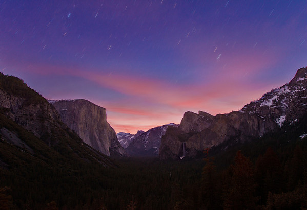 "This shot was taken from a popular location in Yosemite National Park called ""Tunnel View,"" and was actually taken well before sunrise. Star trails and a sunrise aren't things that normally go together. If the sun is rising, you have too much light in the sky for star trails. However, if you keep your shutter open for over 5 minutes (339 seconds to be exact) at just the right time starting just before the dawn sky starts to appear, you can capture both in a single frame.   That's exactly what I did here for this image. With the exception of the two trees (that have slightly orange tips) in the foreground, this is a single...  <a href=""http://www.travelcaffeine.com/yosemite-national-park-tunnel-view-star-trails-sunrise/"" rel=""nofollow"">To continue reading about the technique, etc., used on this photo, click to read about it on my blog...</a>"