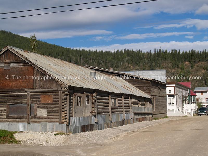 """Log buildings on a dusty old street in Dawson City. <br /> <br /> SEE ALSO:  <a href=""""http://www.blurb.com/b/893025-north-to-alaska"""">http://www.blurb.com/b/893025-north-to-alaska</a>"""