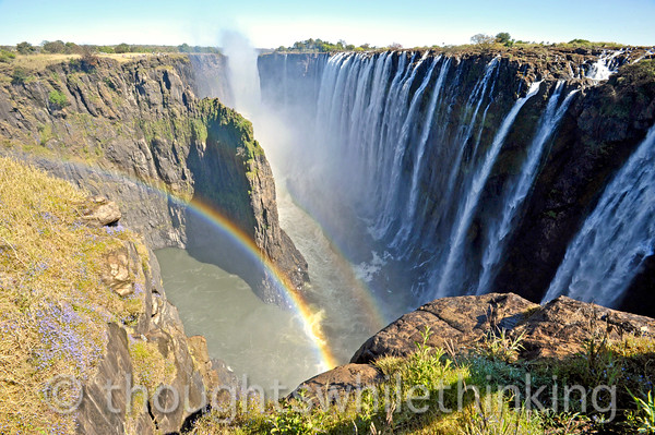 Victoria Falls. Looking west, the falls extends another half a mile beyond what can be seen in this photo, which was taken at the western end of the tourist trail on the Zambian side. Water flows from the upper center of this shot toward the double rainbows. Water from both directions (see prior photo) then flows to the left out of the gorge into the calm area under the larger rainbow and from there into a series of rapids (out of sight) as the Zambezi River continues south.