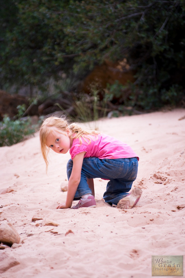 Baby G playing in the sand at the trail head of a slot canyon in Zion National Park.