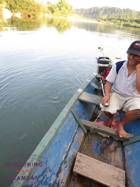 Our driver, taking a call as we cruised downstream.