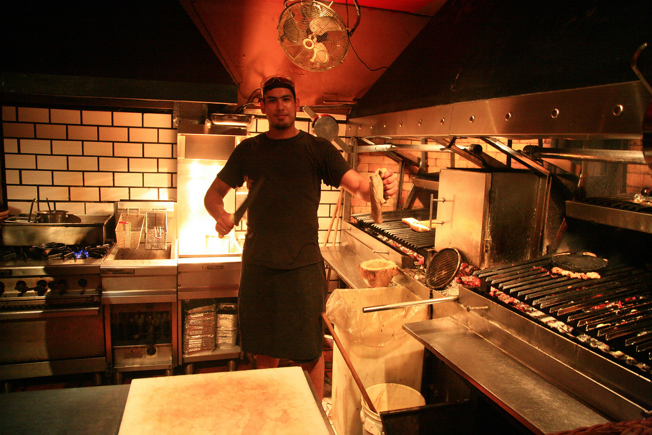 The cook shows off a slab of meat.