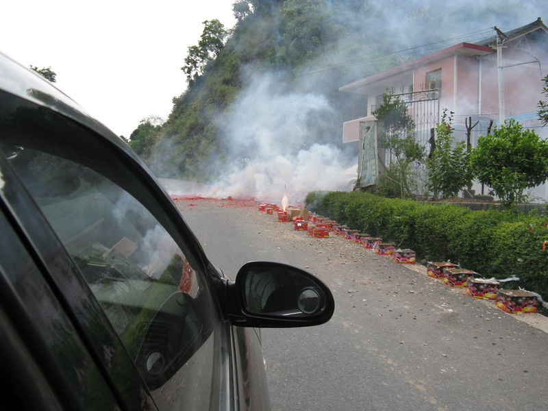 A wedding celebration blocks the road with fireworks