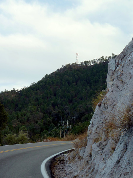 Microwave tower with a hillside.