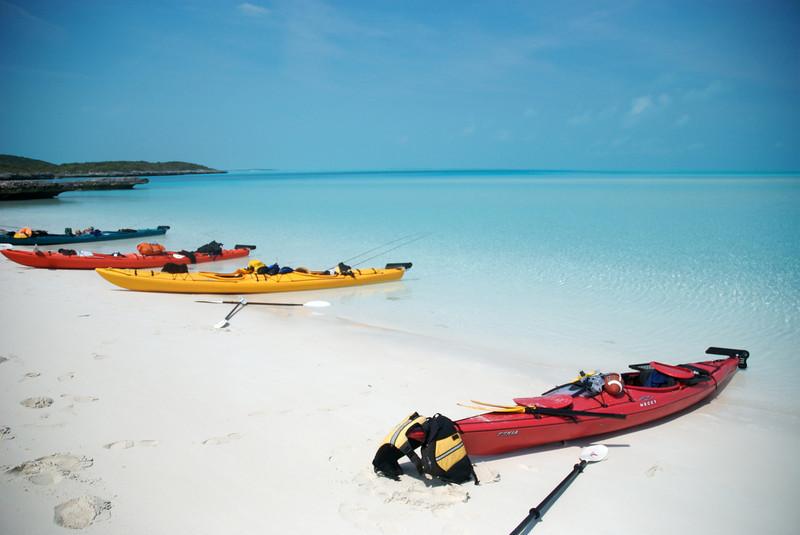 sea kayaks resting on a perfect beach in the exuma islands, bahamas
