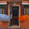 Umbrellas hanging up to dry outside orange house on Burano, Italy