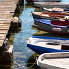 Traditional Greek fishing boats are docked on a small wooden dock at the Greek seaside town of Methoni