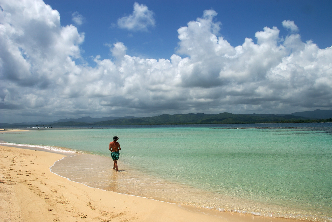 a woman on a remote beach walking in the shallows in the San Blas Islands of Panama