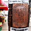 An intricate copper embossed street art poster protests big business at Kensington Market in Toronto, Canada