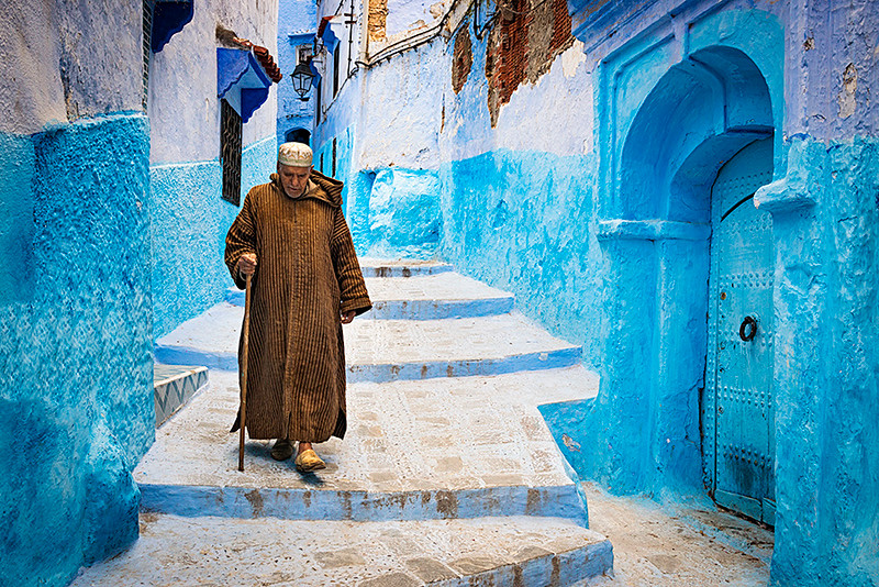 Chefchaouen, Morocco - April 10, 2016: An old man walking in a street of the town of Chefchaouen in Morocco.