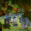 Tombstone of a Revolutionary War soldier seen through the autumn leaves at the cemetery in Woodstock, Vermont.