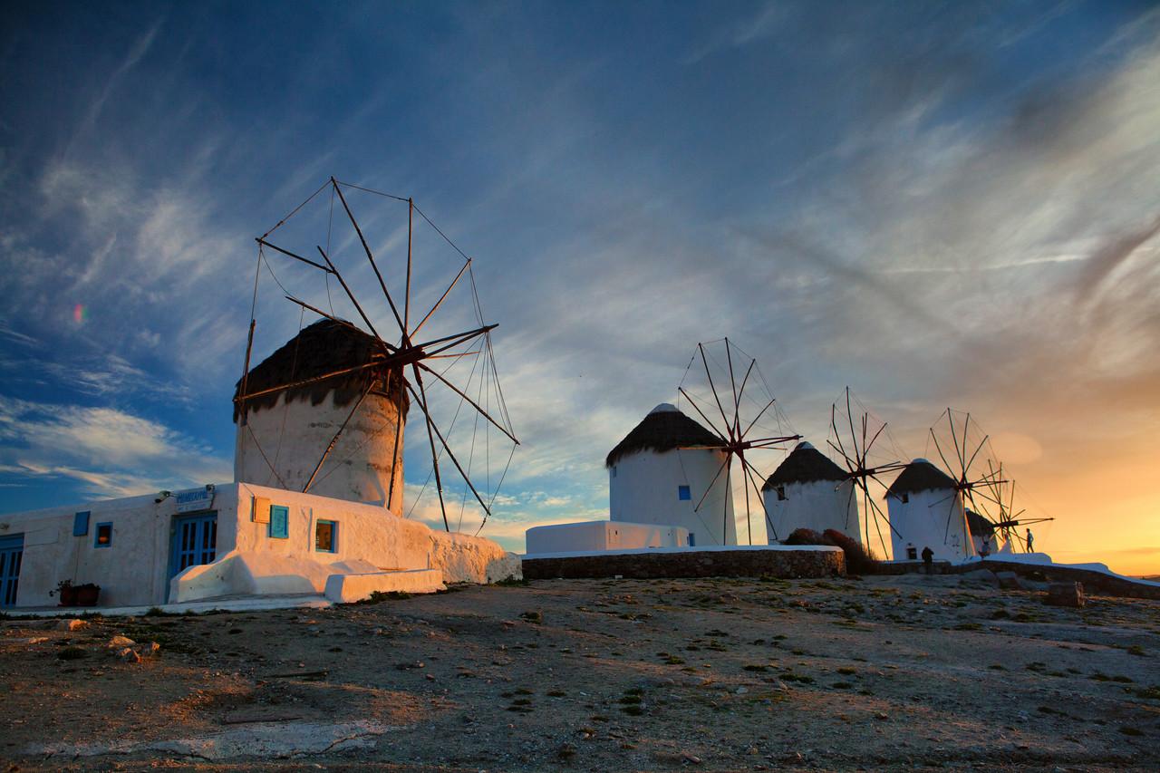 Tourists enjoy the sunset at the windmills of Mykonos, Greece