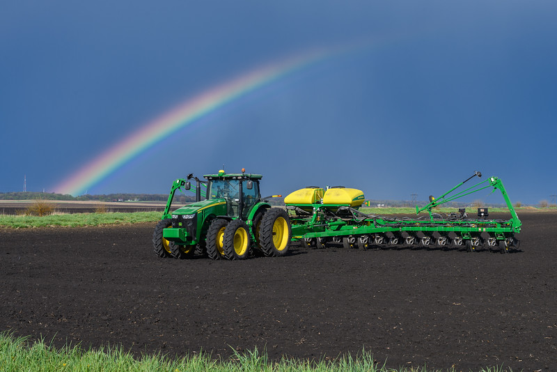 Rainbow over tractor in field in Illinois