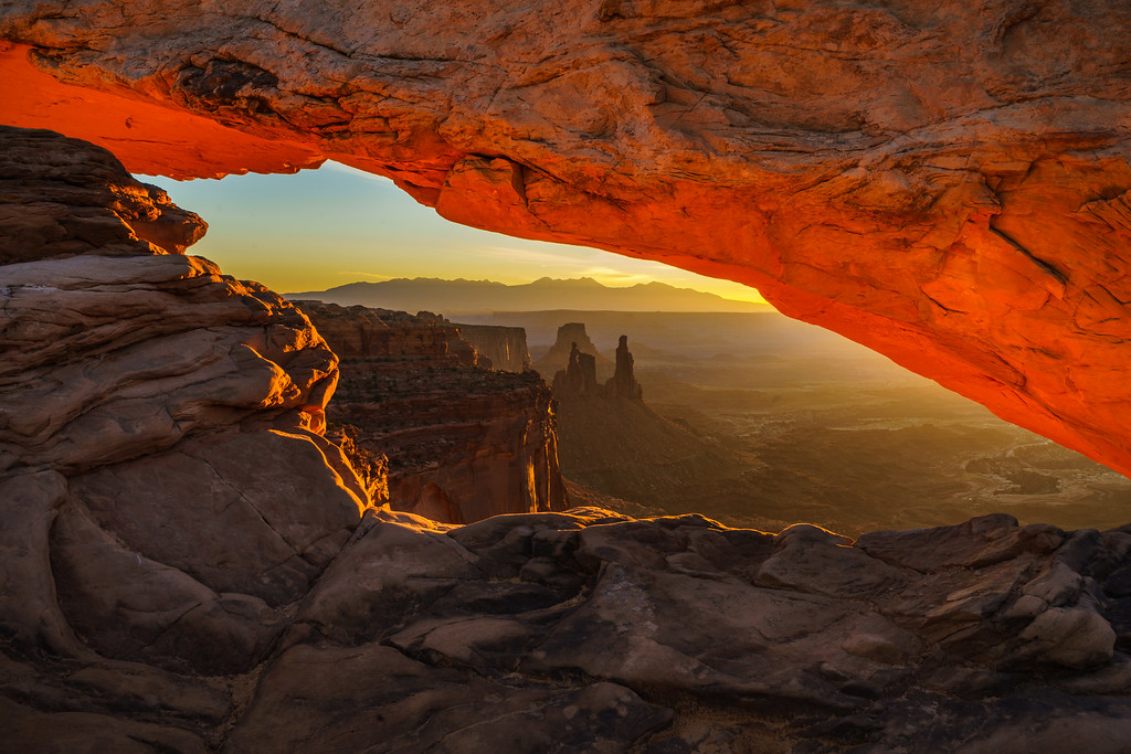 Sunrise lighting up the bottom of Mesa Arch with Monster and Airport Towers silhouetted.