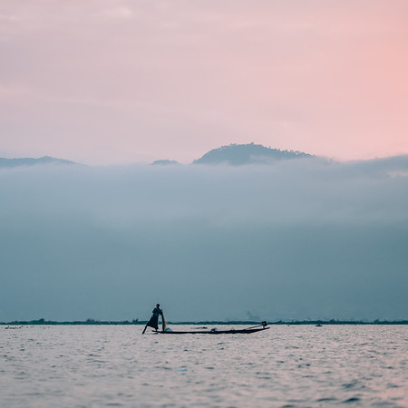 A fisherman navigates Inle Lake in Myanmar before sunrise.