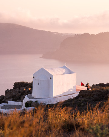 Hikers enjoy the sunset from a tiny chapel above Oia, Santorini.