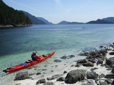 a man kayaks through a calm channel in the discovery islands, british columbia canada