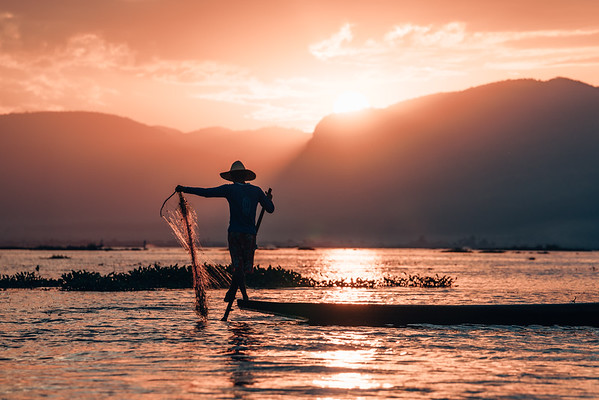 A fishermen rows his wooden boat on Inle Lake as the sun sets. The fishermen of Inle Lake are famous for their style of leg rowing.