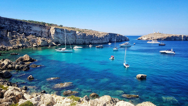 Sailboats and swimmers enjoy a quiet cove near St. Paul's Islands and the coastal town of Xemxija on Malta