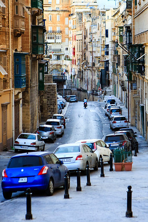 A moped rider drives down a colorful street in Valletta's historic distric, Malta.