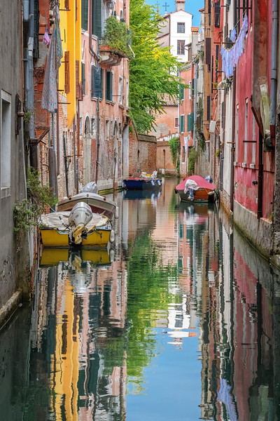 Bright colors from boats, houses and laundry reflected in a canal in Venice, Italy