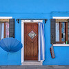 Blue umbrella and blue building on the island of Burano, Italy