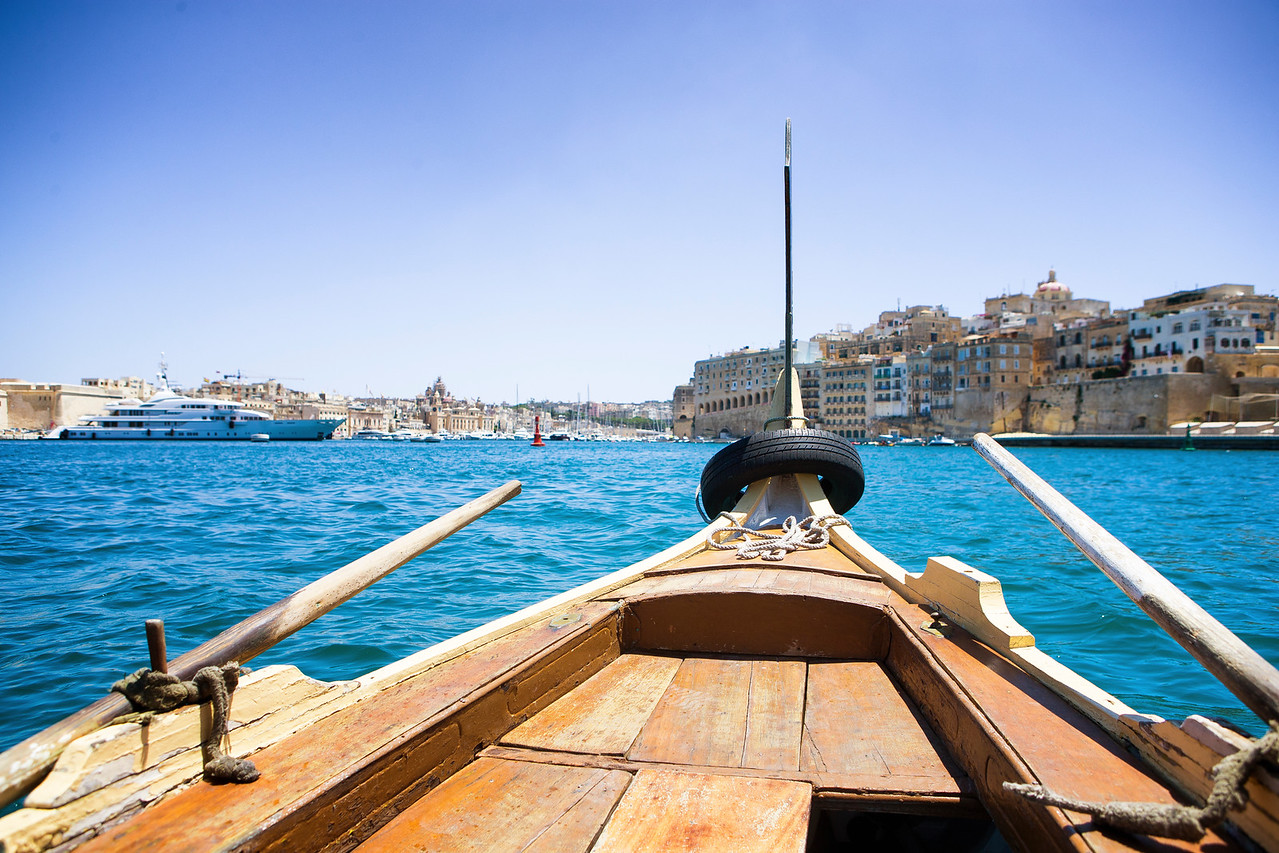 A traditional wooden boat crosses the port of Malta from Valletta to the Three Cities
