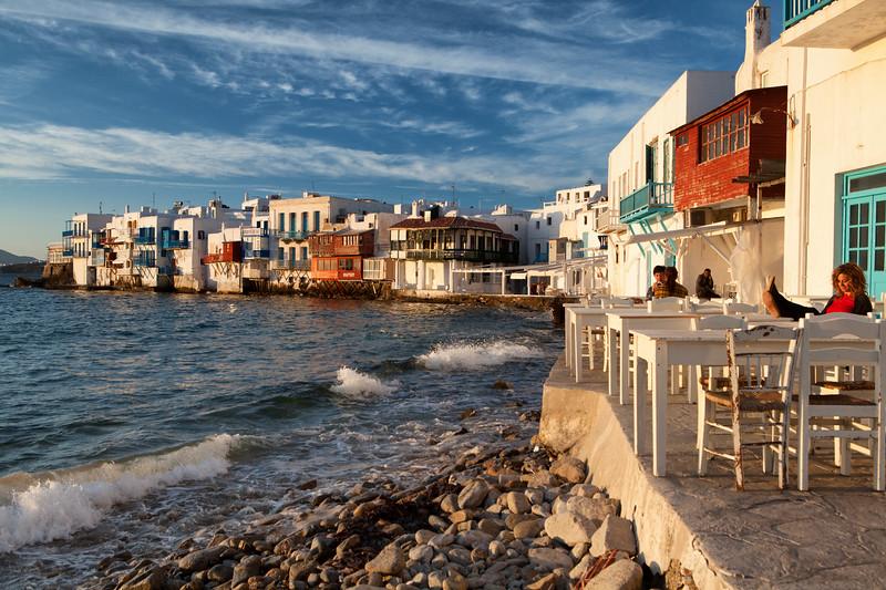 Tourists sit along the Mediterranean Sea near Little Venice on the Greek Island of Mykonos