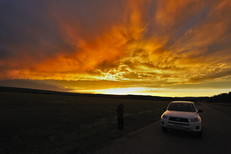 Visitor and car at dusk in Yellowstone national park
