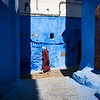 Chefchaouen, Morocco - April 10, 2016: A woman walking in a street of the town of Chefchaouen in Morocco.