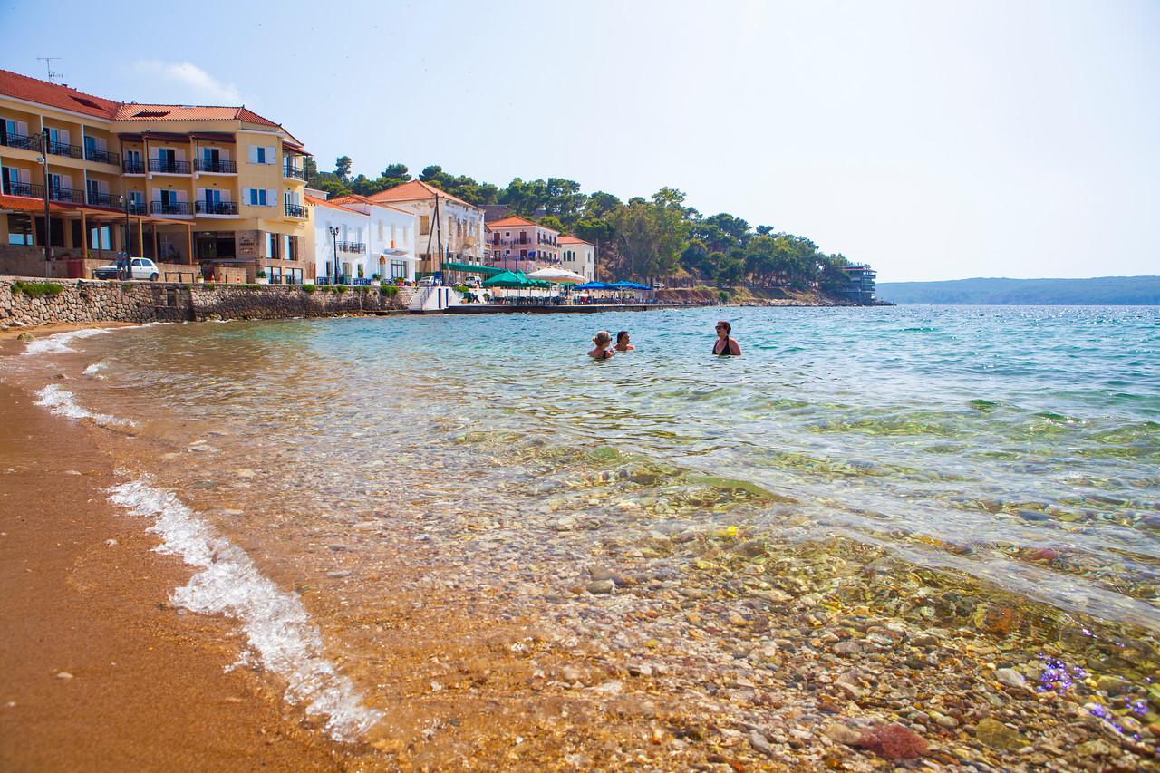 Tourists swim in the Mediterranean Sea near the coastal Greek village of Pylos