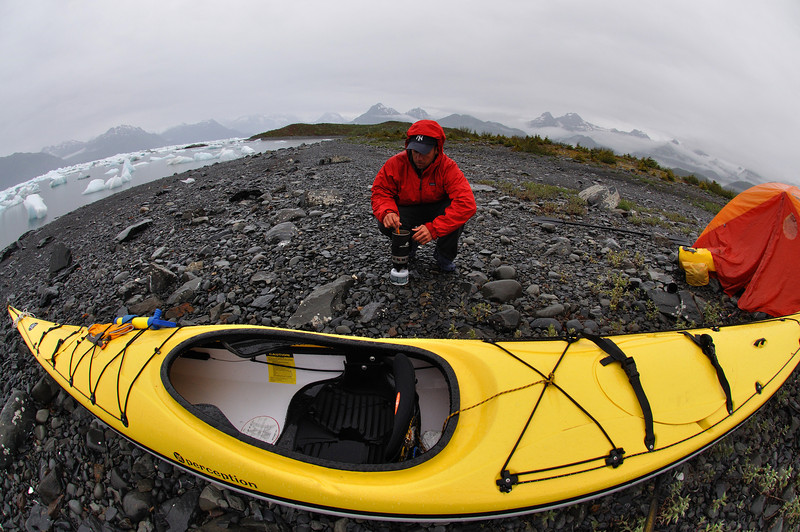 A sea kayaker prepares dinner near the Columbia glacier in Prince William Sound, Alaska