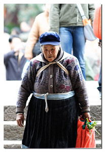 Local old lady walked back home after shipping in a local farm market