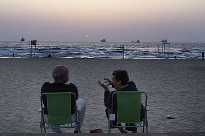 Commercial vessels are seen at sea while an Israeli couple relax during sunset on the beach near the port in the southern Israeli city of Ashdod May 29, 2010. Preparations are underway to intercept a fleet of ships carrying hundreds of pro-Palestinian activists and thousands of tonnes of supplies destined for the Hamas-run Gaza Strip. AFP PHOTO / MARCO LONGARI (Photo credit should read MARCO LONGARI/AFP/Getty Images)