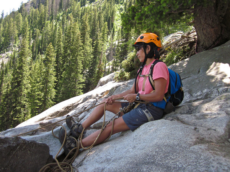 Elise displays a good belay stance -- feet braced against the rock in front, the climbing rope firmly around her waist, with her hands taking up the slack in the rope as the climber ascends toward her.