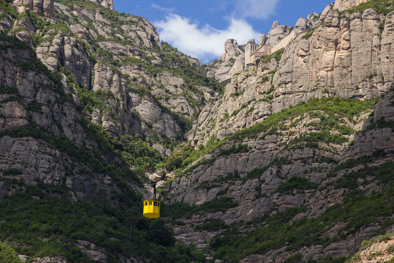 After a train ride outside the city, we take a cable car to the top of Montserrat Mountain, the site of a Benedictine abbey, Santa Maria de Montserrat, which hosts the Virgin of Montserrat sanctuary and which is identified by some with the location of the Holy Grail in Arthurian myth. We're on a mission to find it!