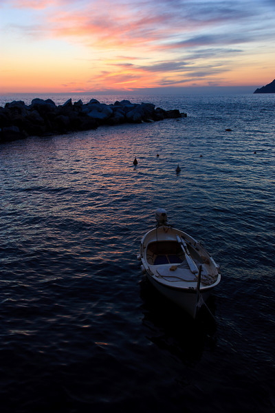A small breakwater protects the tiny harbor at Manarola, where a few boats are moored.