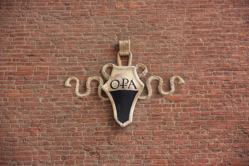 This symbol is seen in many locations in and around the Duomo. It stands for Opera della Metropolitana, which is the administrative body of the Siena Cathedral.