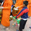 tak bat - the ritual of giving food to the monks<br /> (NB: the small boy is taking the monks' overflow)