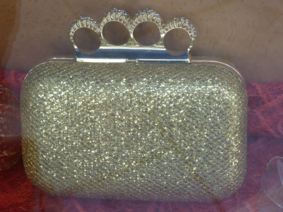 I saw this in a shop window and thought it was curious: looks like an evening bag with a handle of brass knuckles.